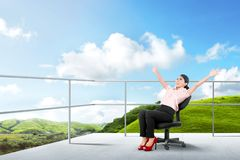 Pretty asian business woman sitting on the chair and relaxing on the terrace royalty free stock photo