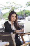 A pretty asian business woman using laptop outdoor Stock Photography