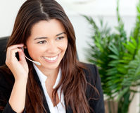 Pretty asian businesswoman putting earpiece Royalty Free Stock Photos