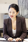 Pretty asian businesswoman typing Stock Photos