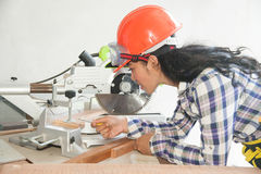 Pretty Asian carpenter woman is marking on wood. Royalty Free Stock Images