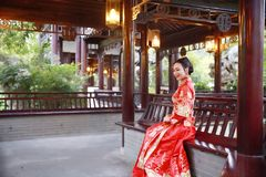 Chinese woman wearing typical Chinese bride`s silk red dress, sitting on classical garden royalty free stock photo