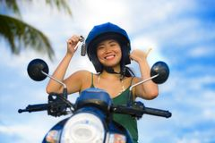 Pretty Asian Chinese girl showing key of new motorbike wearing motorcycle safety helmet smiling proud in scooter buying and rental Royalty Free Stock Photo