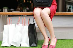 Pretty Asian Chinese modern fashionable woman girl legs shopping card bags in a mall store casual buyer closeup High-heeled shoes. There is a Asian Chinese stock photos