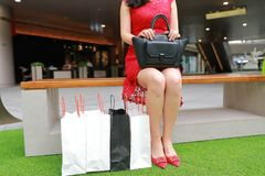 Pretty Asian Chinese modern fashionable woman girl legs shopping card bags in a mall store casual buyer closeup High-heeled shoes. There is a Asian Chinese stock photo
