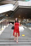 Pretty Asian Chinese modern fashionable woman girl smile shopping card bag in a mall store casual buyer walk on stairs adult. There is a Asian Chinese modern royalty free stock images