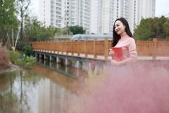 Pretty Asian Chinese woman beautiful girl outdoor sit on grass lawn in a park garden feel carefree caucasian pasttime read book stock image