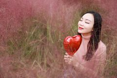 Pretty Asian Chinese woman girl closed freedom dream pray flower field fall park grass lawn hope nature red love shape on her hand stock photography