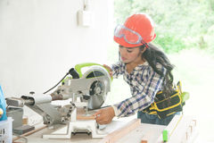 Pretty Asian female carpenter using Electric Sander for wood. Stock Photography