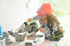 Pretty Asian female carpenter using Electric Sander for wood. Stock Photos