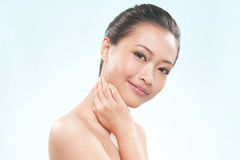 Pretty Asian Female smiling touching her neck Stock Photos