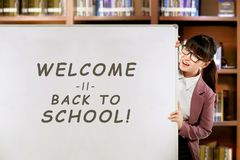 Pretty asian female teacher with Welcome back to school message royalty free stock images