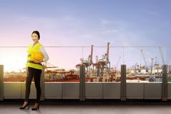 Pretty asian female worker with safety vest holding the hard hat standing on office terrace. With dock and sunset view background royalty free stock photography