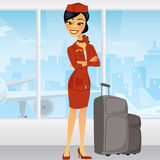 Pretty Asian Flight Attendant in airport. Pretty Asian Flight Attendant with luggage and an airplane in the window behind her Royalty Free Stock Photography