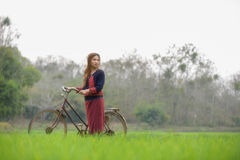 Pretty asian girl with bicycle in field Royalty Free Stock Photography