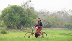 Pretty asian girl with bicycle in field Royalty Free Stock Photos
