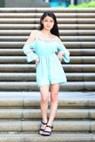 Pretty Asian girl. In a blue dress pose on the stairs Royalty Free Stock Images