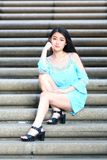 Pretty Asian girl. In a blue dress pose on the stairs Royalty Free Stock Photography