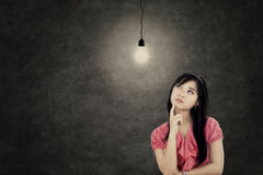 Pretty Asian girl with bright lamp. Portrait of young Asian businesswoman thinking idea while looking up with bright lightbulb Stock Photos
