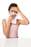 Pretty Asian girl Caught Cold. Sneezing into Tissue. Stock Photo