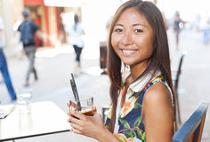 Pretty asian girl drinking on terrace Royalty Free Stock Image