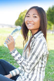 Pretty asian girl drinking water in a park Royalty Free Stock Photography