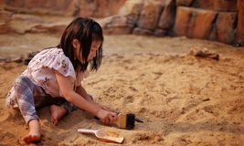 A young Asian girl playing in a sandbox with a modeled dinosaur fossil using brush and shovel