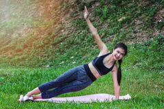 Pretty asian girl practicing the side plank royalty free stock image