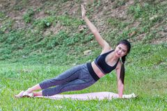 Pretty asian girl practicing the side plank yoga pose stock photo
