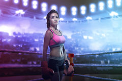 Pretty asian girl in red boxing gloves posing in the boxing ring Stock Images