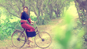 Pretty asian girl sit on bike in park Royalty Free Stock Images