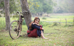 Pretty asian girl sit next to tree and bicycle Stock Image