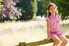 Pretty Asian Girl Sitting On Fence In Countryside Stock Image