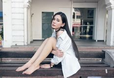Pretty asian girl sitting on a public bench Stock Image