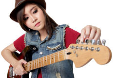 Pretty Asian girl tuning her guitar, on white background. Pretty Asian girl in jeans jacket and fedora hat tuning her electric guitar, on white background royalty free stock photography