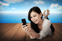 Pretty asian girl using cellphone on the wooden floor Royalty Free Stock Photo