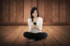 Pretty asian girl using cellphone on the wooden floor Royalty Free Stock Photos