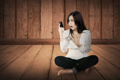 Pretty asian girl using cellphone on the wooden floor. Telecommunication concept Royalty Free Stock Photos