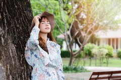 Pretty asian girl in vintage dress leaning against on the tree and relaxing stock photo