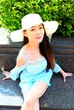 Pretty Asian girl. Wearing hat in a blue  dress Royalty Free Stock Photo