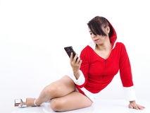 Pretty Asian model wearing Christmas uniform checks on her mobile phone. Pretty Asian model wearing Christmas uniform  wears sexy high heels and looks at her Royalty Free Stock Image