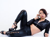 Pretty Asian model wearing sexy clothes uses mobile phone Royalty Free Stock Photography