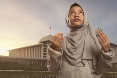 Pretty asian muslim girl in veil praying to god Royalty Free Stock Image