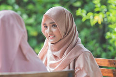 Pretty asian muslim woman in cafe with friend Stock Images