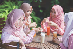 pretty asian muslim woman having fun in cafe together with friends stock photography