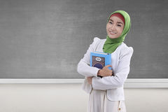 Pretty asian muslim woman holding the holy book Koran Royalty Free Stock Images