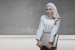 Pretty asian muslim woman holding a laptop Stock Images