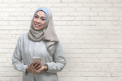 Pretty asian muslim woman with mobile phone on her hands Royalty Free Stock Photo
