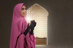 Pretty asian muslim woman raising hand and praying stock photography