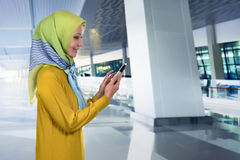Pretty asian muslim woman touching her mobile phone Royalty Free Stock Photo